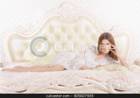 Young woman lying on  bed  stock photo, Beautiful young woman lying on soft beige bed with laptop by Ruslan Huzau