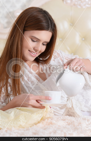 Young woman lying on  bed  stock photo, Beautiful young woman lying on soft beige bed and drinking tea by Ruslan Huzau