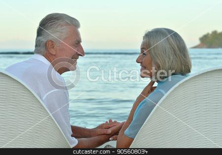 Senior couple on beach stock photo, Portrait of a senior couple resting on beach by Ruslan Huzau