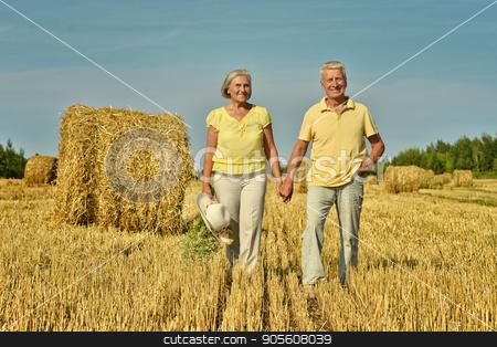 Senior couple on mowed field of wheat  stock photo, Happy senior couple on mowed field of wheat with hay by Ruslan Huzau