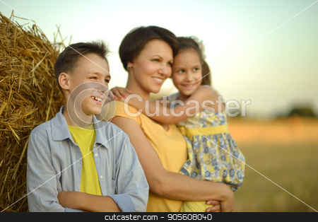 Mother with children near stack of hay  stock photo, Mother with children standing near stack of hay by Ruslan Huzau