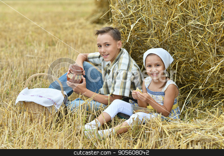 Brother and sister having lunch  stock photo, Brother and sister having lunch while sitting near stack of hay by Ruslan Huzau