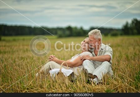 Senior couple on mowed field of wheat stock photo, Happy senior couple on mowed field of wheat by Ruslan Huzau