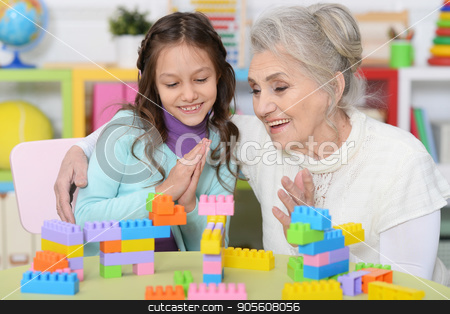 Grandmother playing with granddaughter stock photo, Portrait of a grandmother playing with her little granddaughter by Ruslan Huzau