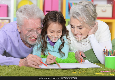 Girl with grandparents drawing picture stock photo, Little girl with grandparents lying on floor and drawing picture by Ruslan Huzau