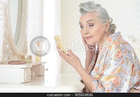 Senior woman applying makeup stock photo, Senior woman applying makeup in front of mirror by Ruslan Huzau