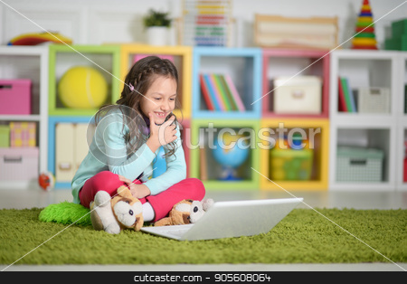 Cute little girl with  laptop  stock photo, Cute little girl with modern laptop on floor by Ruslan Huzau