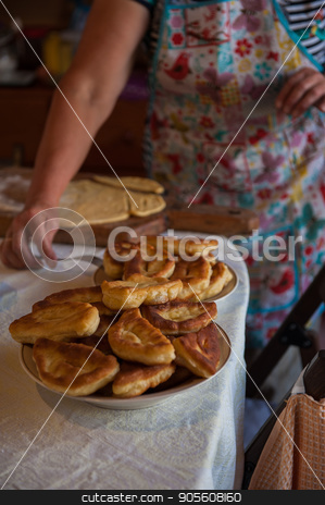 Grandmother bakes pies stock photo, Grandmother bakes pies on the pan and serves to the table by olinchuk