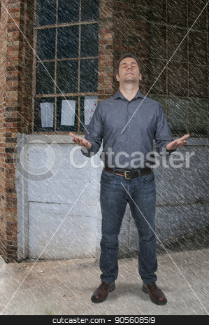 Handsome Man Standing in the rain stock photo, Attractive handsome American or European man standing in the rain with outstretched arms by Robert Byron
