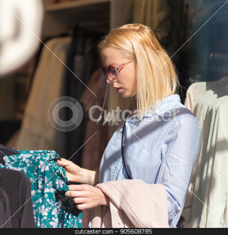 Beautiful woman shopping fashionable clothes in clothing store. stock photo, Woman shopping clothes. Female shopper looking at fashionable clothes indoors in clothing store. by kasto
