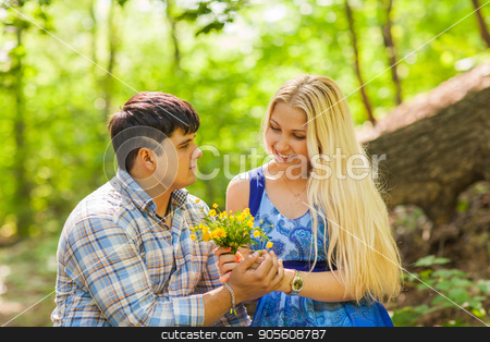 Young man giving a flower dandelion to girlfriend outdoors stock photo, Young man giving a flower dandelion to girlfriend outdoors by Satura86