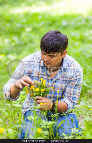 Young man picking up flowers for his woman stock photo, Young man picking up flowers for his woman by Satura86