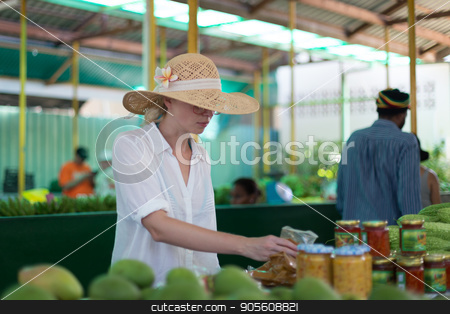 Traveler shopping on traditional Victoria food market, Seychelles. stock photo, Female traveler wearing elegant colonial style white tunic and hat buying fresh tropical fruit on traditional Victoria food market on Seychelles islands. by kasto