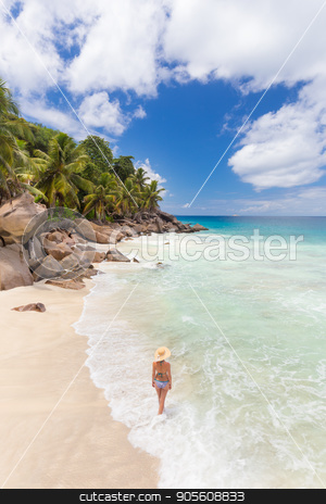 Woman enjoying Anse Patates picture perfect beach on La Digue Island, Seychelles. stock photo, Woman wearing retro striped bikini and beach hat, enjoying amazing view on Anse Patates beach on La Digue Island, Seychelles. Summer vacations on picture perfect tropical beach concept. by kasto