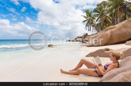 Woman reading book on picture perfect beach Anse Patates on La Digue Island, Seychelles. stock photo, Woman reading book on perfect tropical beach of Anse Patates on La Digue Island, Seychelles. Summer vacations on picture perfect tropical beach concept. by kasto