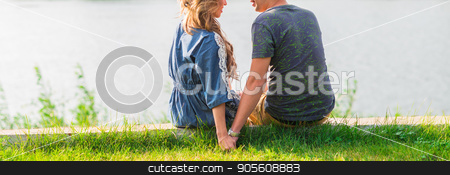 Close-up of young couple is romantic in the park on a lake. Man and woman sit in the summer sun in the green grass stock photo, A young couple is romantic in the park on a lake. Man and woman sit in the summer sun in the green grass by Satura86