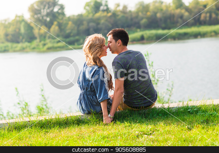 A young couple is romantic in the park on a lake. Man and woman sit in the summer sun in the green grass stock photo, A young couple is romantic in the park on a lake. Man and woman sit in the summer sun in the green grass by Satura86