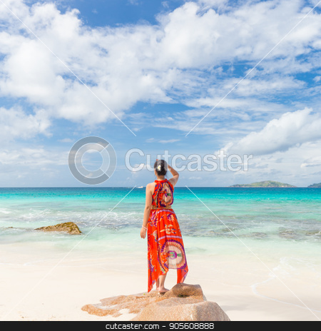 Woman enjoying Anse Patates picture perfect beach on La Digue Island, Seychelles. stock photo, Traditinaly dressed local woman wearing long floral summer dress and hat looking at sea on Anse Patates beach, La Digue Island, Seychelles. Summer vacations on picture perfect tropical island concept. by kasto