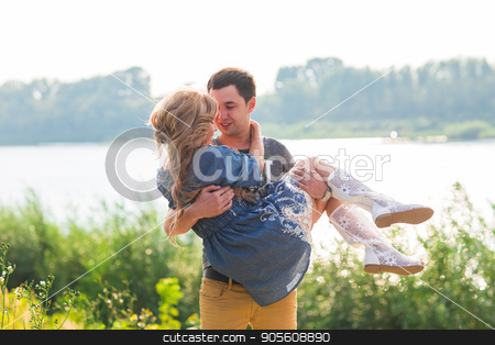 Man holding woman in his arms on the beach of the river on a sunny day stock photo, Man holding woman in his arms on the beach of the river on a sunny day by Satura86