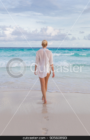 Woman on summer vacations at tropical beach of Mahe Island, Seychelles. stock photo, Woman wearing white loose tunic over bikini on Mahe Island, Seychelles. Summer vacations on picture perfect tropical beach concept. by kasto