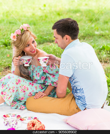 Beautiful Young Couple Having Picnic in Countryside. Happy Family Outdoor. Smiling Man and Woman relaxing in Park. Relationships stock photo, Beautiful Young Couple Having Picnic in Countryside. Happy Family Outdoor. Smiling Man and Woman relaxing in Park. Relationships by Satura86