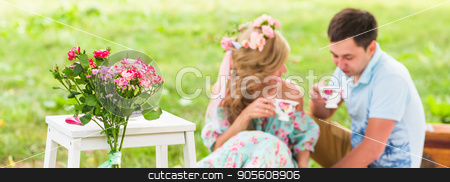 Happy Couple Having Romantic Picnic. Focus on flowers. selective focuse stock photo, Happy Couple Having Romantic Picnic in Countryside by Satura86
