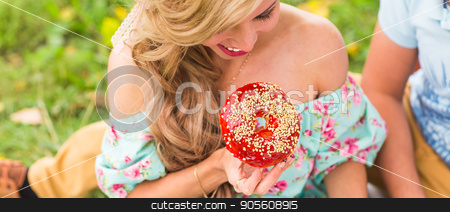 Close-up of young beautiful woman holding a donut. Picnic in nature stock photo, young beautiful woman holding a donut. Picnic in nature by Satura86