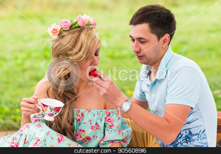 Handsome man is feeding his beautiful woman with a delicious donut in picnic on nature stock photo, Handsome man is feeding his beautiful woman with a delicious donut in picnic on nature by Satura86