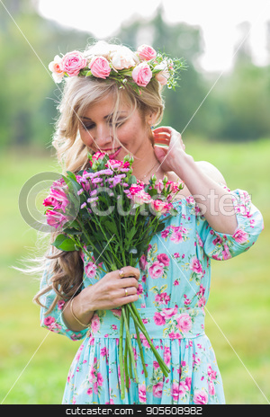 Beautiful blonde girl holding bouquet of flowers at the countryside stock photo, Beautiful blonde girl holding bouquet of flowers at the countryside by Satura86