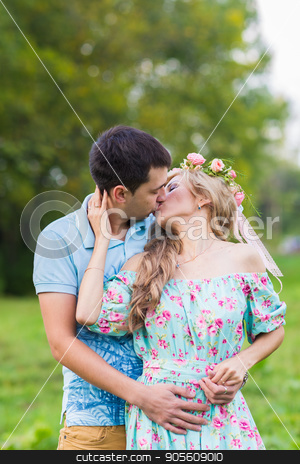 happy young couple kissing and hugging on nature stock photo, happy young couple kissing and hugging on nature by Satura86