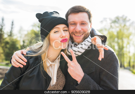 Happy young couple embracing smiling, showing victory sign
