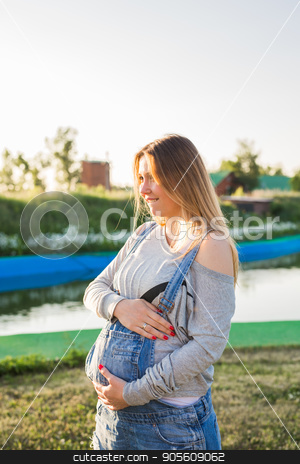 Pregnant woman hugging her belly outdoors stock photo, Pregnant young woman hugging her stomach outdoors by Satura86