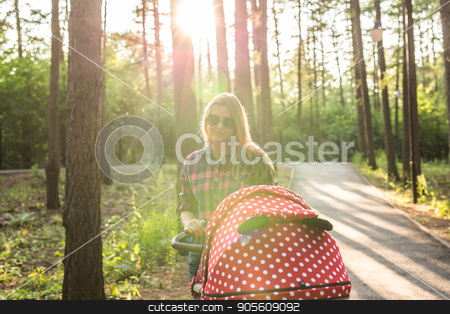 Mother walking with a stroller in the park stock photo, Mother walking while pushing a stroller in the park by Satura86