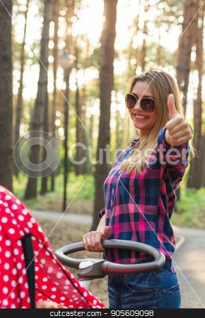 Happy motherhood concept - Woman with pram showing thumbs up outdoors stock photo, Happy motherhood concept - Woman with pram showing thumbs up outdoors by Satura86