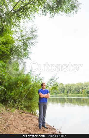 Young man standing in front of beautiful lake stock photo, Traveler man standing in front of beautiful lake by Satura86