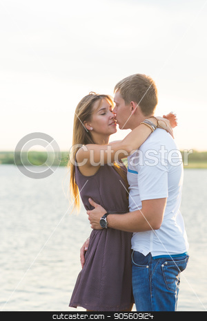 Young couple in love outdoors embracing together at lake stock photo, Young couple in love outdoors embracing and laughing together at lake by Satura86