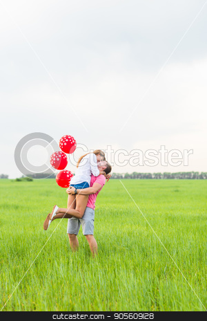 happy couple in love holding red balloon stock photo, happy couple in love holding red balloon in nature by Satura86