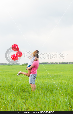 happy couple of man and woman in love dressed in country style holding red balloon