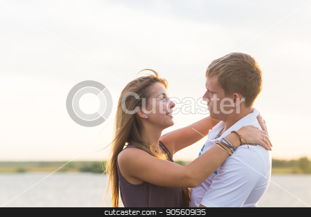 Young couple in love outdoors embracing and laughing together at lake stock photo, Young couple in love outdoors embracing and laughing together at lake by Satura86
