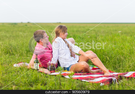 Young couple in summer meadow, man and woman having romantic picnic stock photo, Young couple in summer meadow, man and woman having romantic picnic by Satura86