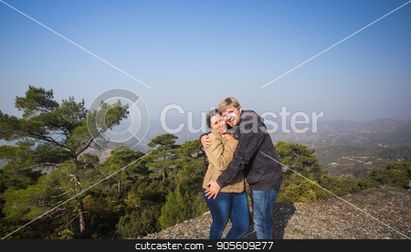 Loving young couple travellers on a mountain, hugging and looking in camera, love and travel concept stock photo, Loving young couple travellers on a mountain, hugging and looking in camera, love and travel concept by Satura86