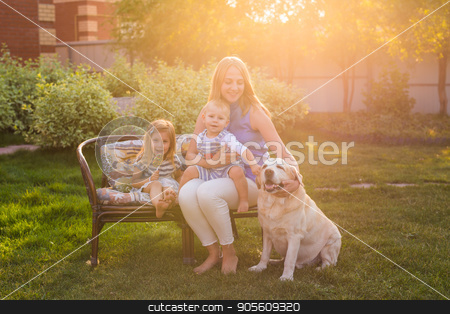 Happy mother and two children with Golden Retriever dog in the garden stock photo, Happy mother and two children with Golden Retriever dog in the garden by Satura86