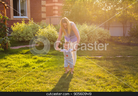 beautiful mother is walking on with her little baby boy son with first steps stock photo, beautiful mother is walking on with her little baby boy son with first steps by Satura86