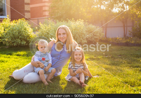 Happy mother and two children in the garden stock photo, Happy mother and two children in the garden by Satura86