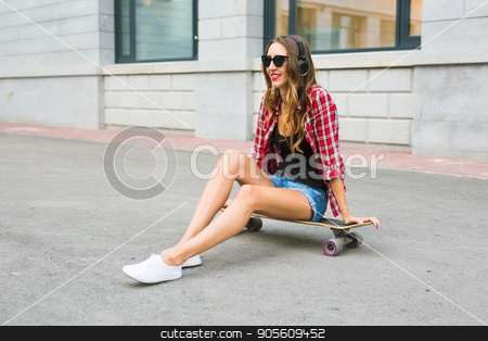 Beautiful and sexy girl sitting on the skateboard stock photo, Beautiful and sexy girl sitting on the skateboard by Satura86
