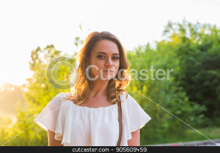 Summer woman enjoying her time outside in park with sunset in background stock photo, Smiling summer woman with hat. Laughing young woman enjoying her time outside in park with sunset in background by Satura86
