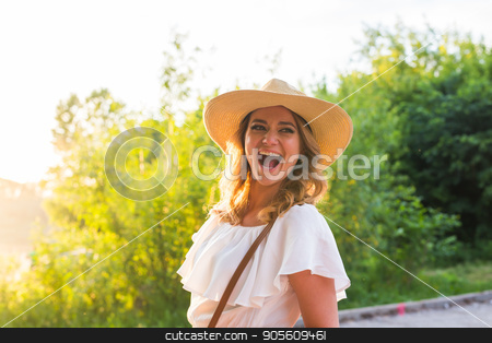 Laughing young woman enjoying her time outside in park with sunset in background stock photo, Laughing young woman enjoying her time outside in park with sunset in background by Satura86