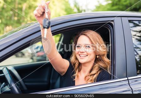 Beautiful young woman driver showing car keys in hand stock photo, Beautiful young woman driver showing car keys in hand by Satura86