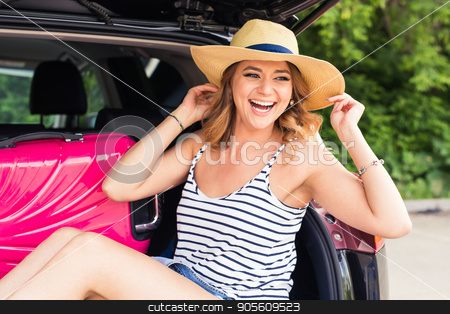 Young laughing woman sitting in the open trunk of a car. Summer road trip stock photo, Young laughing woman sitting in the open trunk of a car. Summer road trip by Satura86