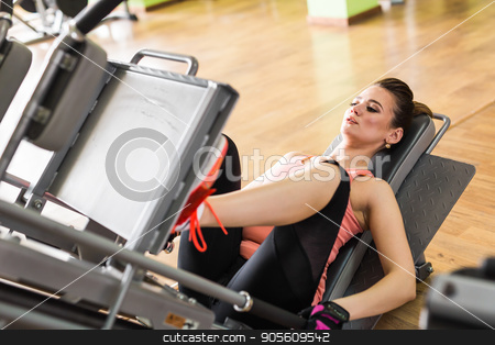 Fit young woman doing leg presses in the gym stock photo, Side view of a fit young woman doing leg presses in the gym by Satura86